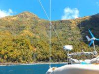 Steiniger Strand und hohe Vulkanberge hinter Gegenwinds Heck
